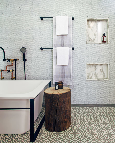 """Encaustic floor tiles, along with hexagonal marble wall tiles and marble shower niches, contrast beautifully with the industrial plumbing fittings and black metal towel rails."""
