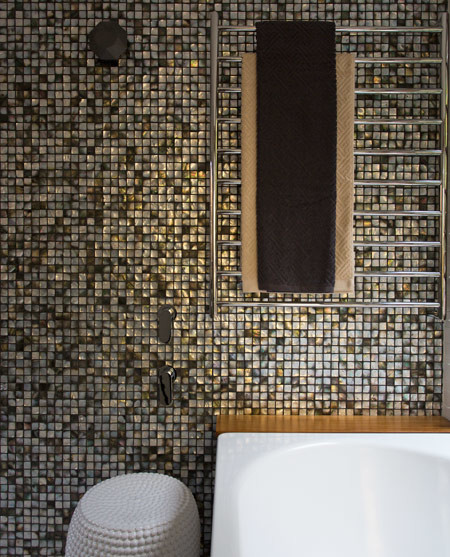 """Feature mosaic tiles create a dramatic contrast to the light-filled and otherwise very white master ensuite."""
