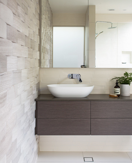 """In the guest bathroom, the travertine tiles, difficult to clean, are used only on a feature wall."""